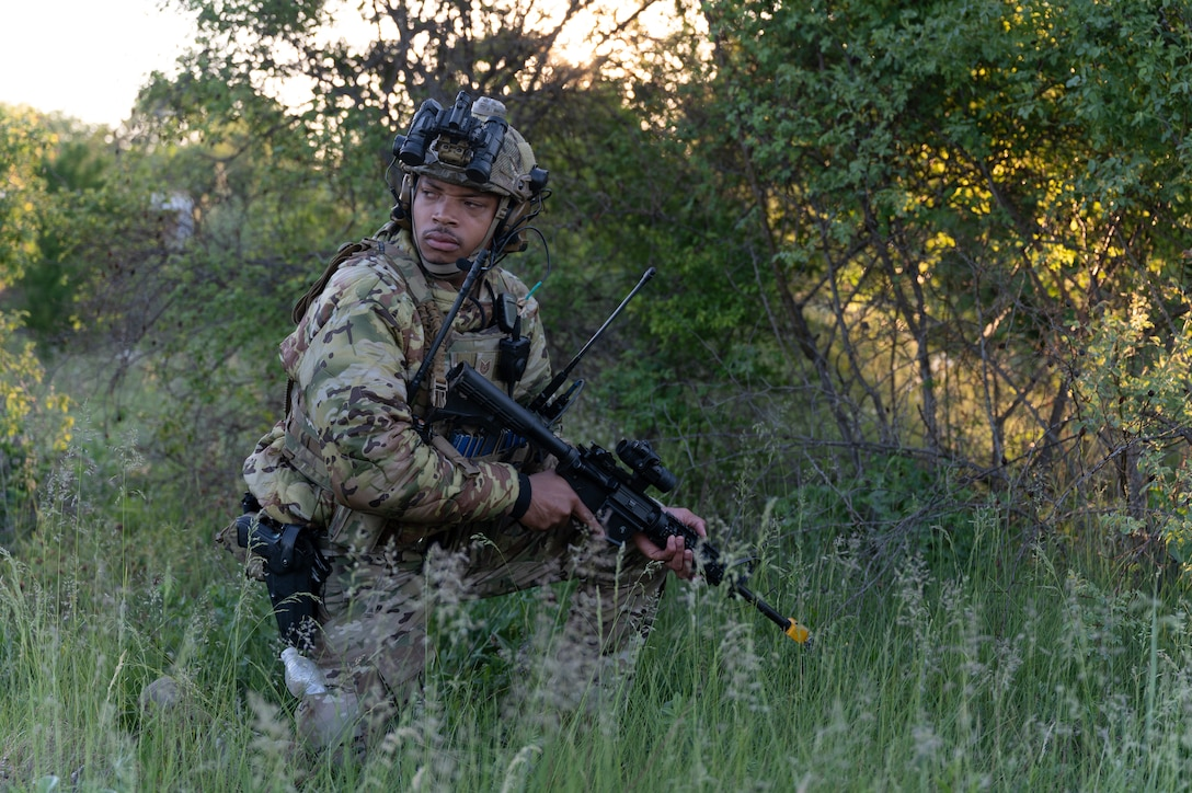 An airman standing in a field with combat gear.
