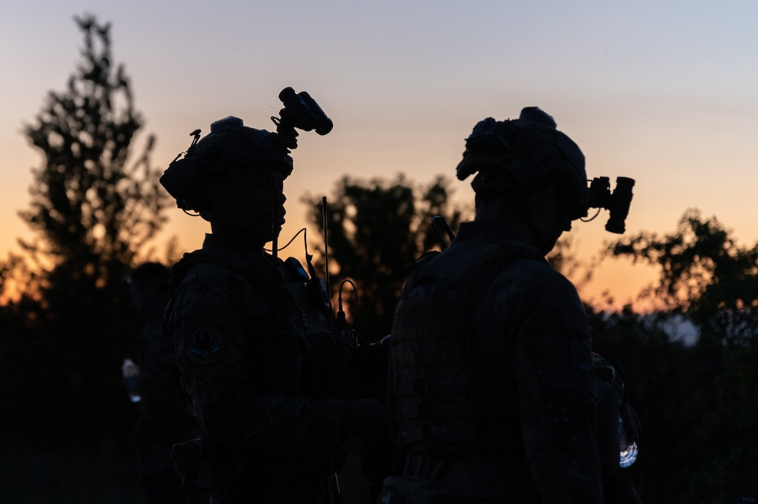 The silhouettes of two Airmen wearing helmets and night vision goggles.