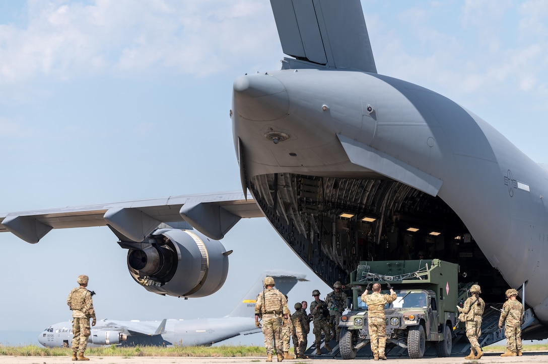 Airmen and Soldiers standing next to an aircraft with its ramp down.