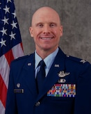 Official Air Force biography photo for Col. Eric Schmidt. looking at the camera in Air Force blues uniform.