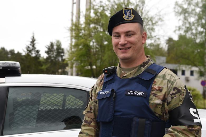 U.S. Air Force Tech. Sgt. Edwin Bowser, 569th U.S. Forces Police Squadron flight sergeant, poses near a patrol car.