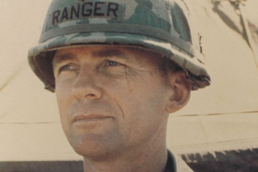 A man wearing a helmet looks to the left.