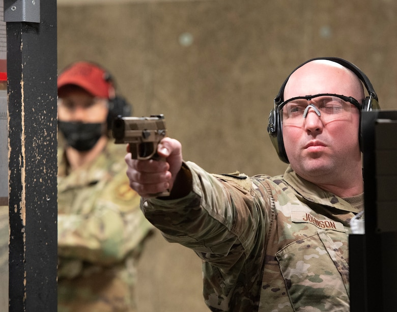 U.S. Air Force Tech. Sgt. Dakota Johnson, 88th Security Forces Squadron, takes aim with his M-18 in the squadron's indoors shooting range on Wright-Patterson Air ForceBase, Ohio, May 11, 2021, as a combat arms instructor looks on. The squadron held a shooting competition as part of its annual Police Week activities. (U.S. Air Force photo by R.J. Oriez)