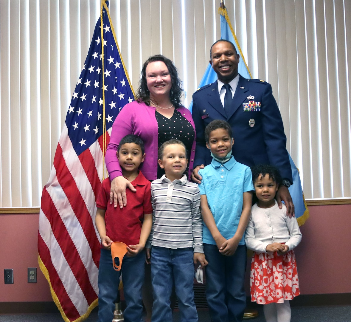a military man in uniform stands with his wife and four kids