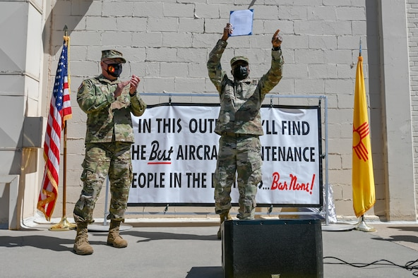 Gen. Nava and Col. Clark stand on a stage celebrating getting 2019 New Mexico State Outstanding Unit award, with a U.S. flag to the left and New Mexico state flag to the right