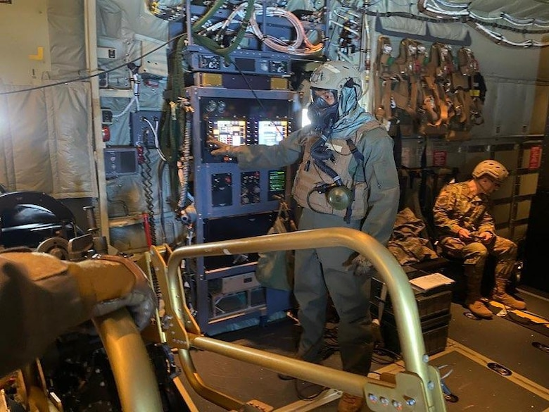 Airman in mask points while operating screen.