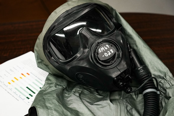 A gas mask on a table next to a piece of paper displaying a graph.