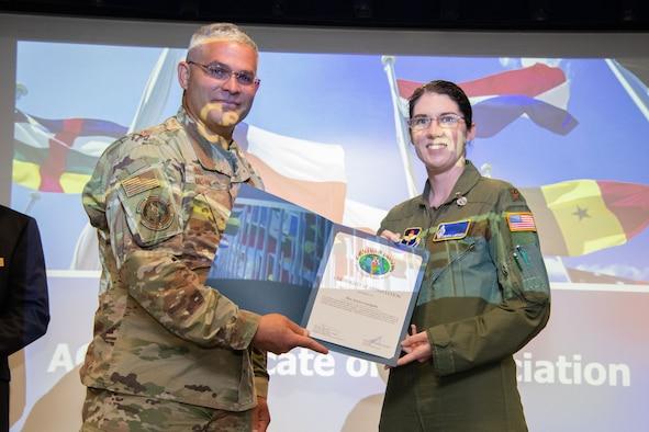 International Officer School Commandant and Air University International Affairs Director Col. Alex Ganster presents a certificate of appreciation to Maj. Amanda LaMonica at Husband Auditorium, Maxwell Air Force Base, Alabama, May 18, 2021.