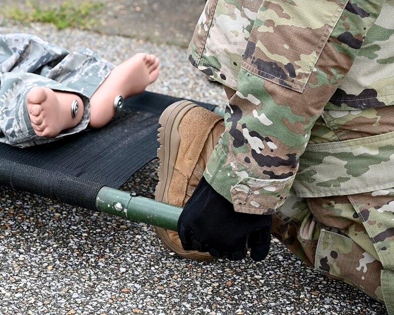 a person prepares to lift a stretcher