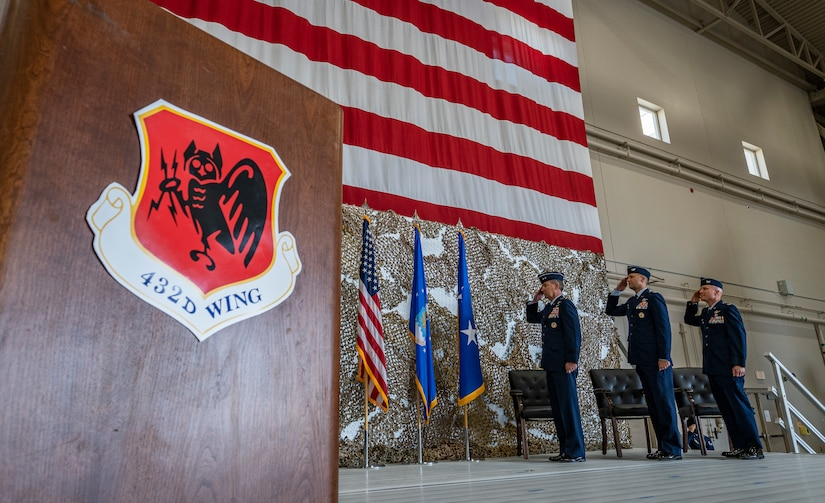 Maj. General Chad P. Franks, Fifteenth Air Force commander, Col. Stephen Jones, outgoing 432nd Wing/432nd Air Expeditionary Wing commander, and Col. Eric Schmidt, incoming 432nd WG/432nd AEW commander salute the American flag during the national anthem during the 432nd WG/432nd AEW change of command ceremony at Creech Air Force Base, Nevada, May 20, 2021.