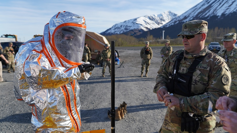 Sgt. 1st Class Brian Miller, 102nd Civil Support Team, Oregon National Guard, senior supply noncommissioned officer, supervises the decontamination process after a team member responded to a simulated incident at the Alaska Railroad train yard in Seward, Alaska, May 18, in support of Exercise ORCA 21. ORCA is a chemical, biological, radioactive, nuclear threats response exercise designed for participants to provide support in the aftermath of hazardous materials incidents. ORCA tests interoperability between agencies, increases opportunities for working relationships, and practices requests for assistance methods. Approximately 250 National Guardsmen from CST units in Alaska, California, Connecticut, Colorado, Idaho, Ohio, Oregon, Rhode Island, South Carolina, South Dakota, Washington, and Wisconsin are in Alaska to participate in Exercise ORCA 2021. Numerous support units and civilian agencies participated in the exercise as well. (U.S. Army National Guard photo by Dana Rosso)