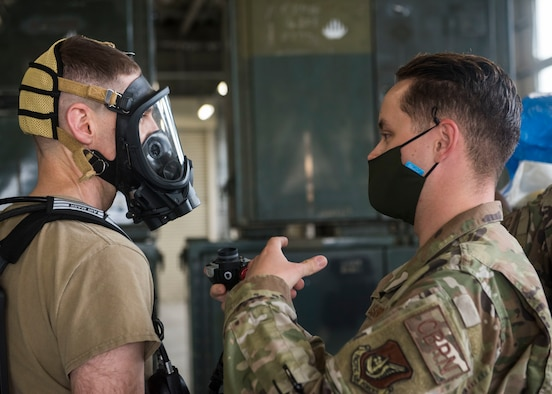 One man in uniform helps another man equip a oxygen mask.