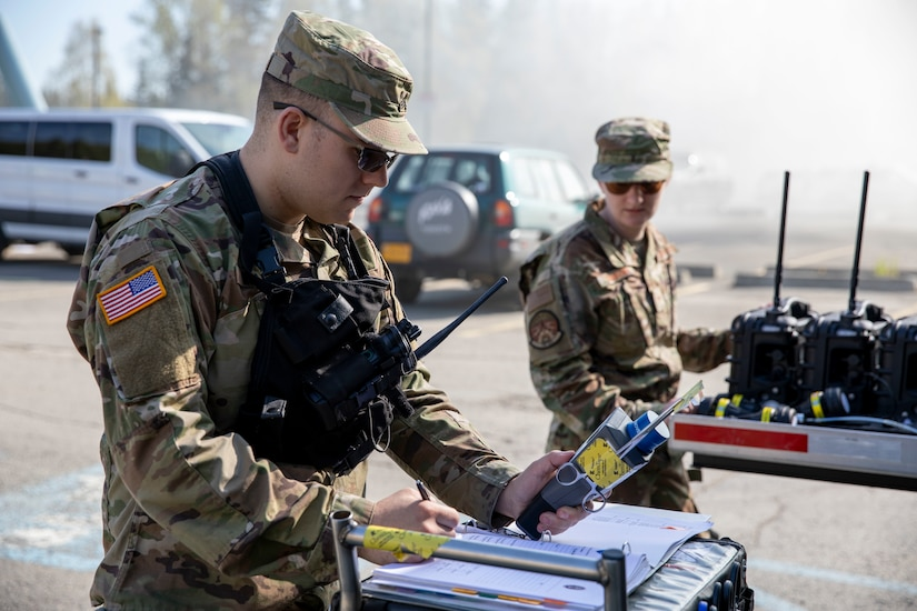 Sgt. Jason Williams, 103rd Civil Support Team, and Senior Airman Scottie Branson, 176th Civil Engineering Squadron, prepare gear to respond to a simulated incident at a parking garage on the University of Alaska Anchorage campus May 18, in support of Exercise ORCA 2021. ORCA is a chemical, biological, radioactive, nuclear threats response exercise designed for participants to provide support in the aftermath of hazardous materials incidents. ORCA tests interoperability between agencies, increases opportunities for working relationships, and practices requests for assistance methods. Approximately 250 National Guardsmen from CST units in Alaska, California, Connecticut, Colorado, Idaho, Ohio, Oregon, Rhode Island, South Carolina, South Dakota, Washington, and Wisconsin are in Alaska to participate in Exercise ORCA 2021. Numerous support units and civilian agencies participated in the exercise as well. (U.S. Army National Guard photo by Spc. Grace Nechanicky)