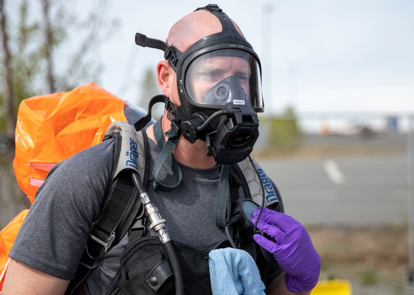 Sgt. Anthony Luiken, 103rd Civil Support Team, performs radio checks through his mask in preparation to respond to a simulated incident in a tower at the Anchorage Fire Training Center, May 19, in support of Exercise ORCA 2021. ORCA is a chemical, biological, radioactive, nuclear threats response exercise designed for participants to provide support in the aftermath of hazardous materials incidents. ORCA tests interoperability between agencies, increases opportunities for working relationships, and practices requests for assistance methods. Approximately 250 National Guardsmen from CST units in Alaska, California, Connecticut, Colorado, Idaho, Ohio, Oregon, Rhode Island, South Carolina, South Dakota, Washington, and Wisconsin are in Alaska to participate in Exercise ORCA 2021. Numerous support units and civilian agencies participated in the exercise as well. (U.S. Army National Guard photo by Spc. Grace Nechanicky)