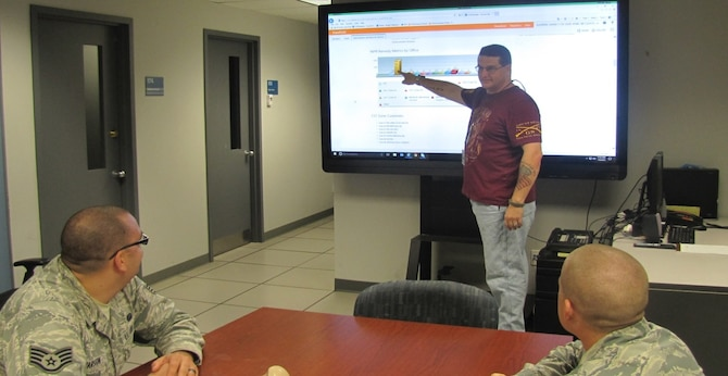 David Slavens, senior duty officer at the 88th Communications Squadron's Cyber Operations Center, leads a discussion with two NCOs on how to prepare remedy tickets for personnel at Wright-Patterson AFB. (Contributed photo)