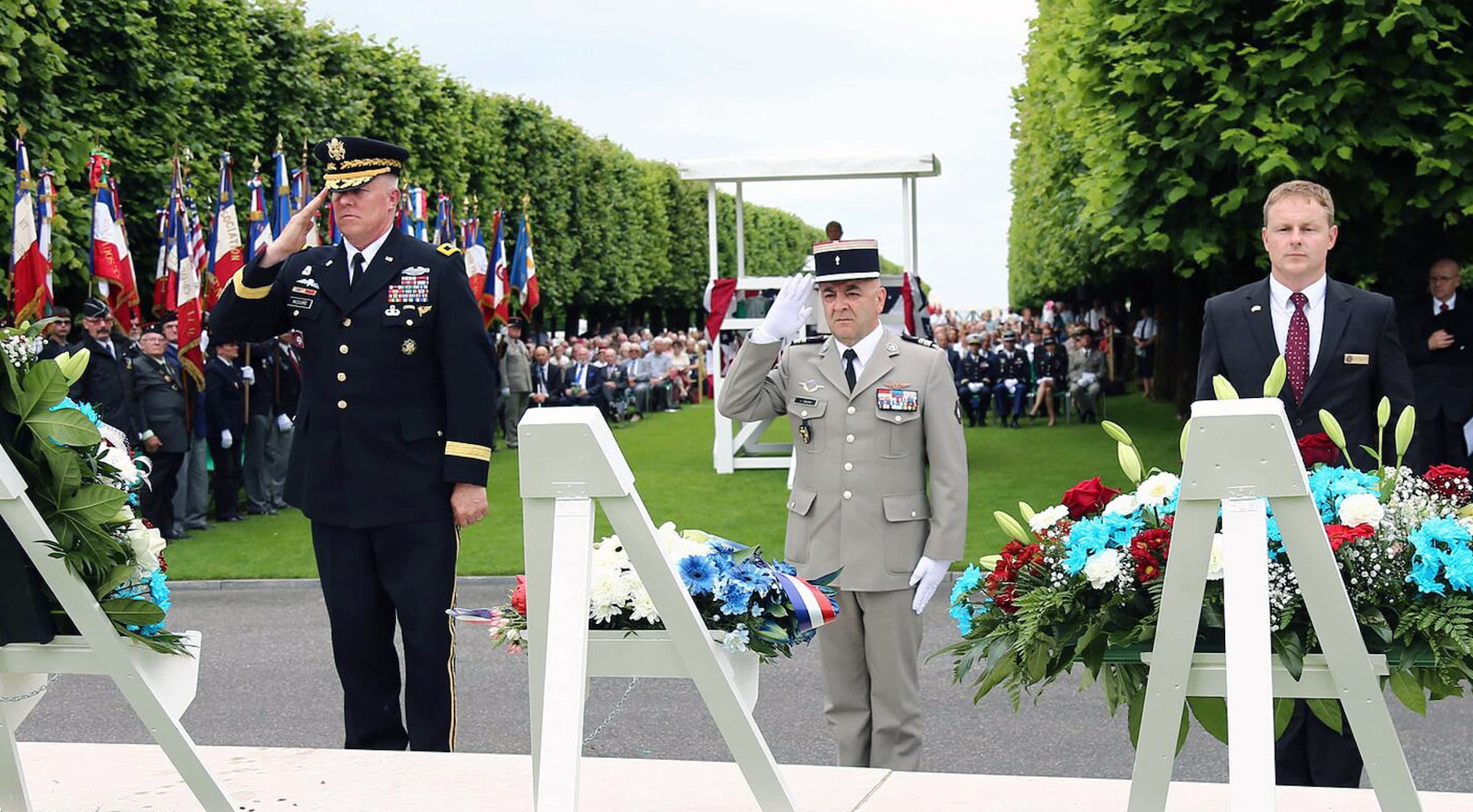 Three men standing in a cemetery. Two military members saluting.