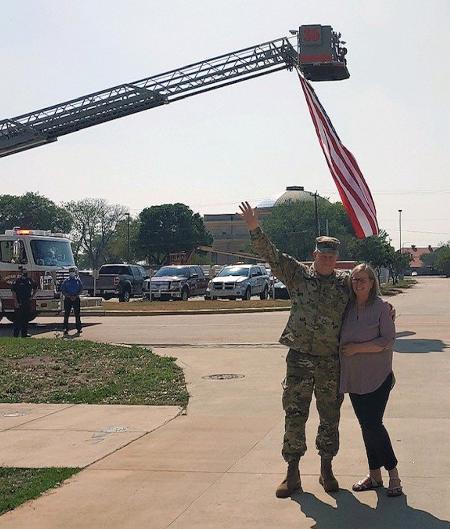 Man and woman waving standing under flag.