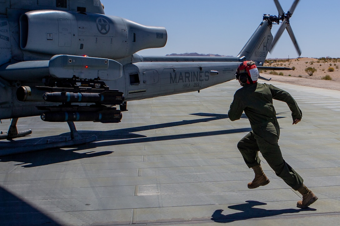 U.S. Marine Corps Lance Cpl. Lauren M. Young, an ordnance team member with Marine Light Attack Squadron (HMLA) 269, runs to an AH-1Z Viper helicopter at Marine Corps Air-Ground Combat Center Twentynine Palms, California, April 28, 2021. HMLA-269 and other squadrons assigned to Marine Aircraft Group (MAG) 29 are training to integrate with and support various Marine ground units as part of Service Level Training Exercise (SLTE) 3-21. SLTE is a series of exercises designed to prepare Marines for operations around the globe by increasing their ability to operate and conduct offensive and defensive combat operations. MAG-29 is a subordinate unit of 2nd Marine Aircraft Wing, the aviation combat element of II Marine Expeditionary Force. (U.S. Marine Corps photo by Lance Cpl. Elias E. Pimentel III)