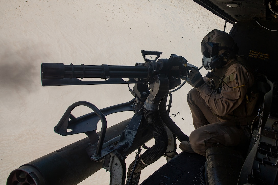 U.S. Marine Corps Sgt. Daniel Fessenden, a crew chief instructor with Marine Light Attack Squadron (HMLA) 269, fires a GAU-17 minigun at a simulated enemy at Marine Corps Air-Ground Combat Center Twentynine Palms, California, April 22, 2021. HMLA-269 and other squadrons assigned to Marine Aircraft Group (MAG) 29 are training to integrate with and support various Marine ground units as part of Service Level Training Exercise (SLTE) 3-21. Marine Corps Air-Ground Combat Center Twenty-nine Palms