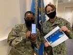 Two masked female officers display their relay mileage totals.