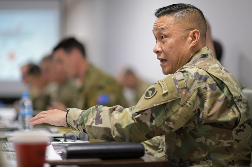 An Army officer speaks during a meeting.