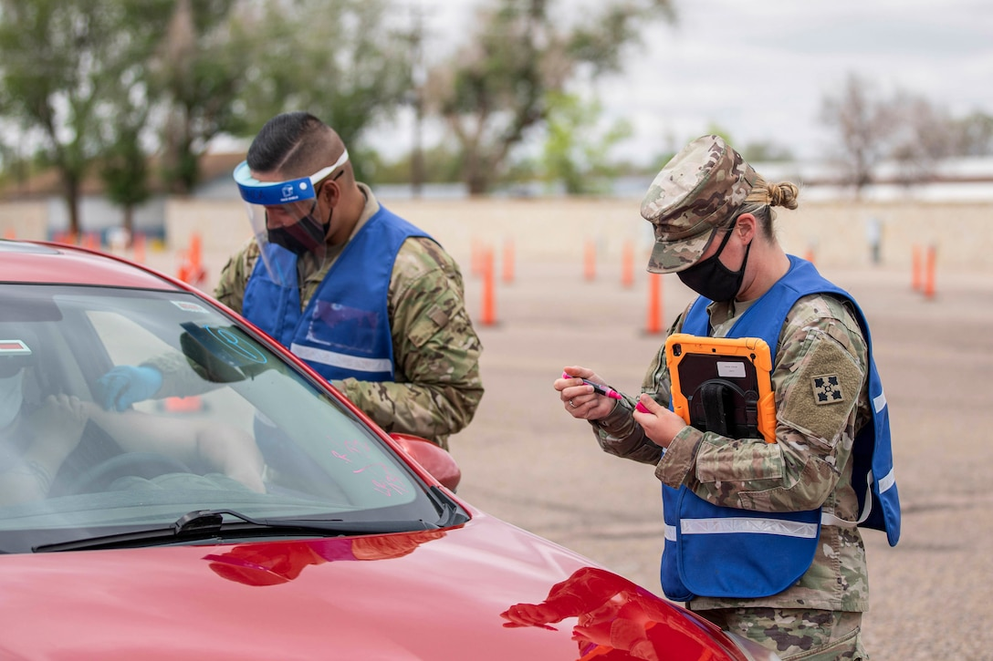 Two soldiers wearing face masks talk to a motorist in a car.