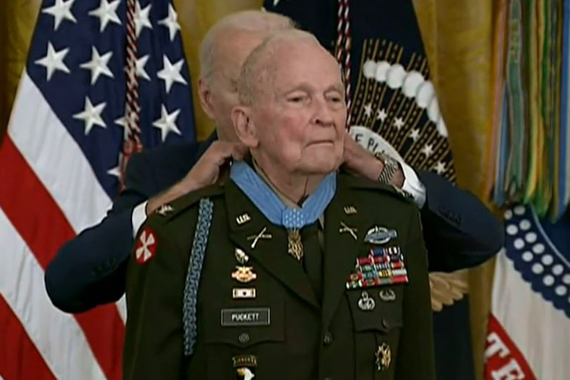 A man places a medal around the neck of another man in a military uniform.