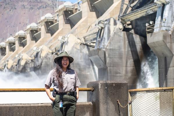 A ranger stands in front of a dam spillway.