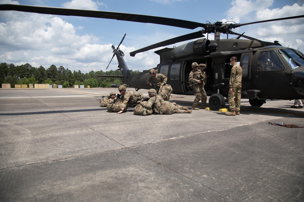 Troops practice drills next to a helicopter.