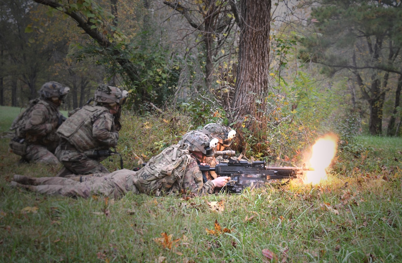 Soldiers in the woods fire weapons.