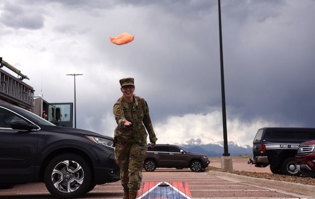 Airman 1st Class Gianina Zielke, 50th Force Support Squadron customer support apprentice, tosses a bean bag during her turn at corn hole during the Schriever Air Force Base Volunteer Appreciation Awards Ceremony, May 14, 2021. Zielke dedicates her free time volunteering at a local rescue mission that provides meals for the homeless. Volunteers from Schriever Air Force Base were recognized for their volunteer work on base and throughout the community. (U.S. Space Force photo by Airman 1st Class Joshua Fontenot)