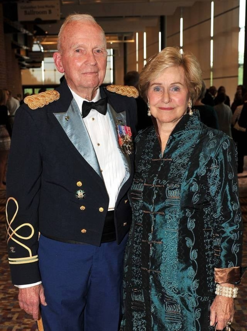 An elderly man in Army dress uniform and an elderly woman pose for a photo.