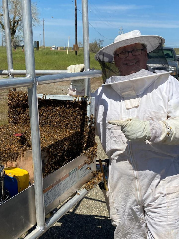 Blaze Baker, 9th Civil Engineer Squadron installation management flight chief, poses with a swarm of bees he caught at Beale Air Force Base, California, April 7, 2021.