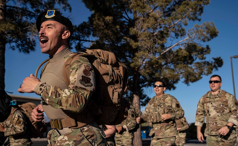 Airmen run and sing during a ruck march.