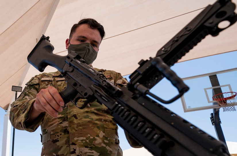 Airman inspects the barrel of a weapon.