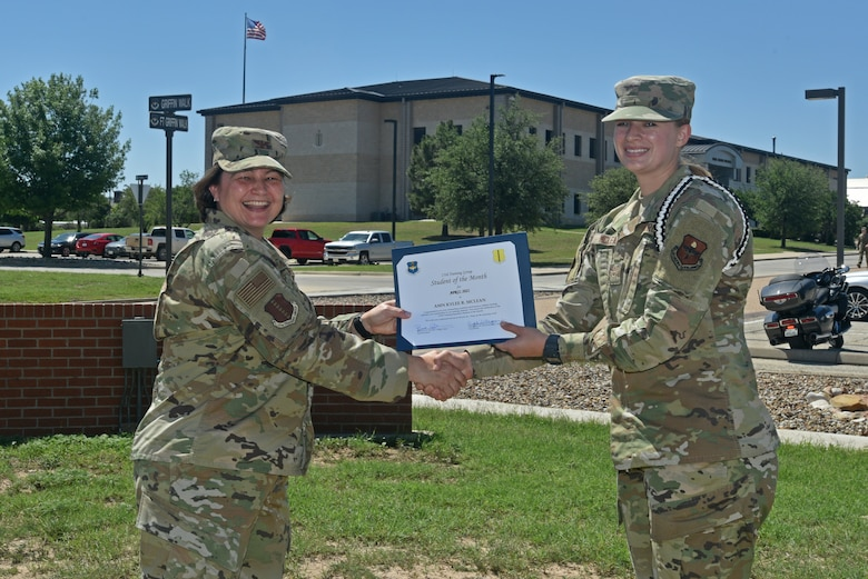 U.S. Air Force Col. Angelina Maguinness, 17th Training Group commander, presents Airman Kylee Mclean, 315th Training Squadron student, the 17th TRG Student of the Month award for April 2021, outside of the Brandenburg Hall on Goodfellow Air Force Base, Texas, May 21, 2021. Mclean worked hard for her award and has shown her dedication to her squadron and the training she received at Goodfellow. (U.S. Air Force photo by Senior Airman Ashley Thrash)