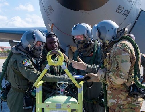 Aircrew and maintenance Airmen from the 91st Air Refueling Squadron (ARS) perform KC-135 Stratotanker aircraft pre-flight checks while wearing aircrew eye and respiratory protection system equipment during a large-scale readiness exercise at MacDill Air Force Base, Florida, May 20, 2021