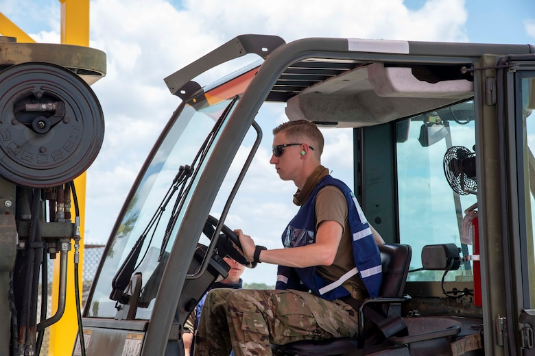 A U.S. Air Force Airman from the 6th Logistics Readiness Squadron (LRS) operates a forklift during phase one of a large-scale readiness exercise, at MacDill Air Force Base, Florida, May 18, 2021. The first phase, focused on rapid mobility of personnel, aircraft and assets. (U.S. Air Force photo by Airman 1st Class Hiram Martinez)