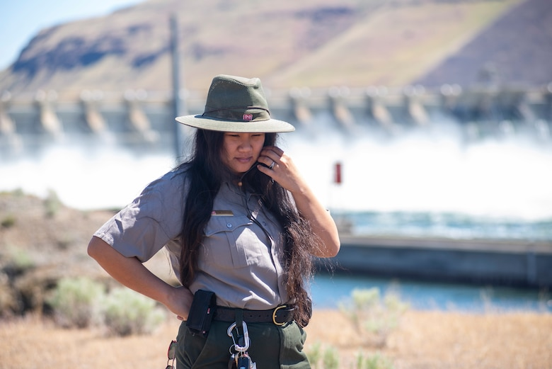 A ranger stands with a dam in the background.