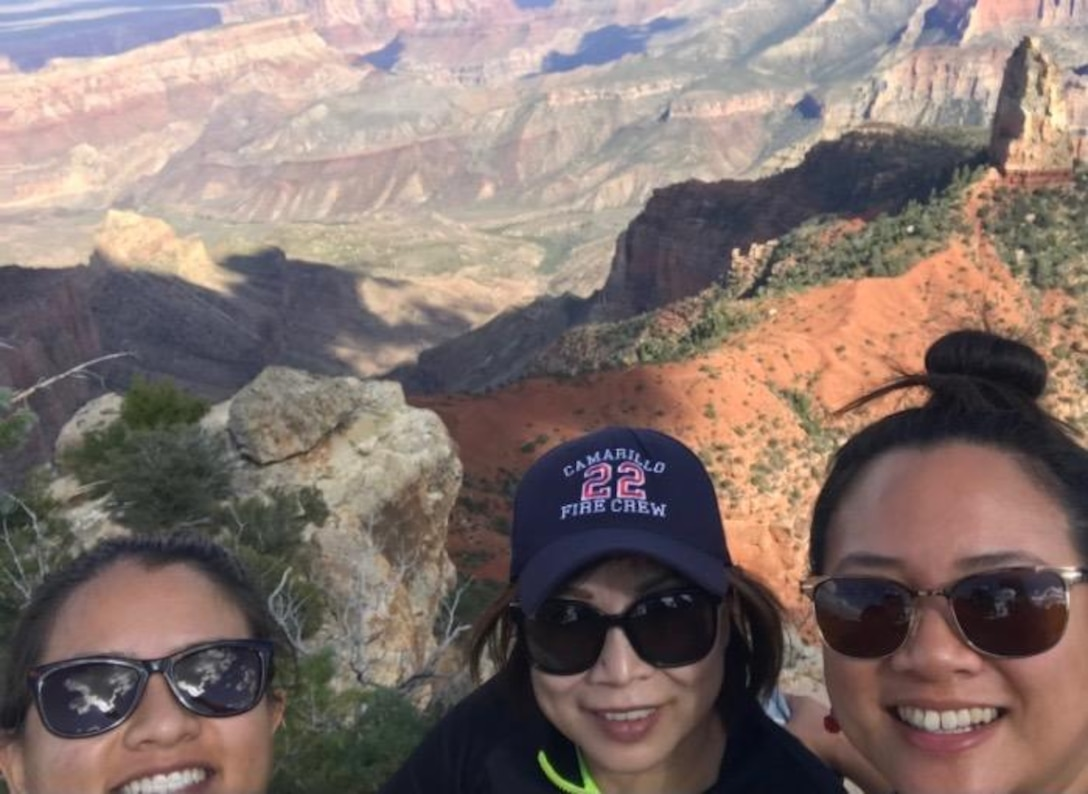 Three people stand together with a view of the Grand Canyon in the background.