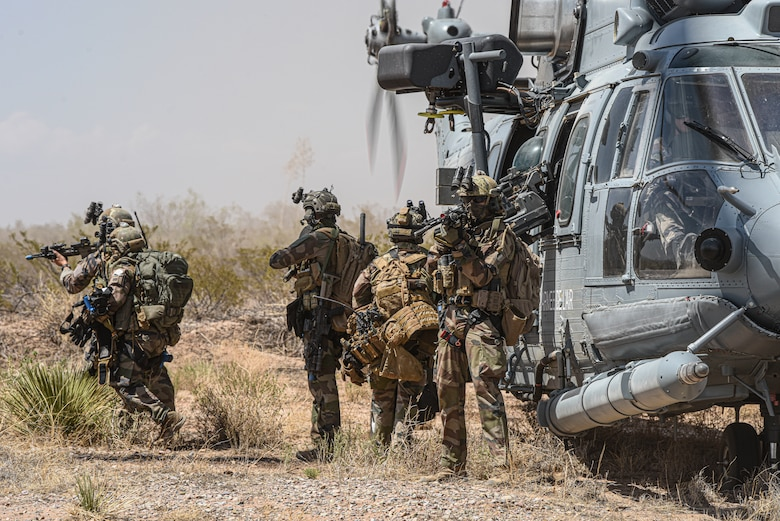 A group of soldiers board a helcopter.