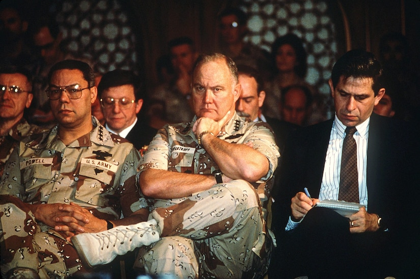 Paul Wolfowitz, under secretary of defense for policy, right, takes notes while Gen. Colin Powell, chairman, Joint Chiefs of Staff, and Gen. Norman Schwarzkopf, Jr., commander-in-chief, U.S. Central Command, listen to Secretary of Defense Dick Cheney answer questions from the media. The men are taking part in a press conference held by U.S. and Saudi Arabian officials during Operation Desert Storm.