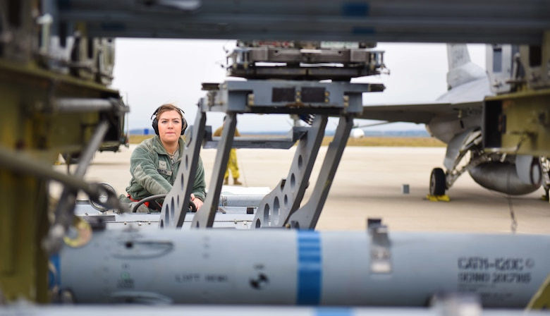 U.S. Air Force Airman 1st Class Nevada Martin, 52nd Aircraft Maintenance Squadron weapons load team  member, operates a bomb lift truck to attach an AIM-120 missile onto an F-16 Fighting Falcon during an  Agile Combat Employment exercise at Spangdahlem Air Base, Germany, Jan. 14, 2020. This exercise  simulated a forward deployed environment for operating without prepositioned equipment. (U.S. Air  Force photo by Staff Sgt. Joshua R. M. Dewberry)