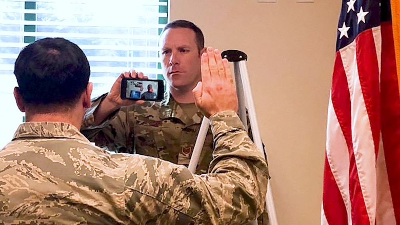 Air National Guard recruiter Kevin O'Brien facilitates a military enlistment utilizing mobile video technology.