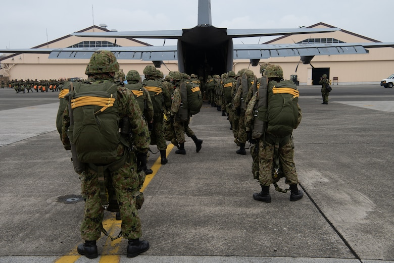 Japan Ground Self-Defense Force soldiers line up outside a U.S. Air Force C-130J Super Hercules aircraft.