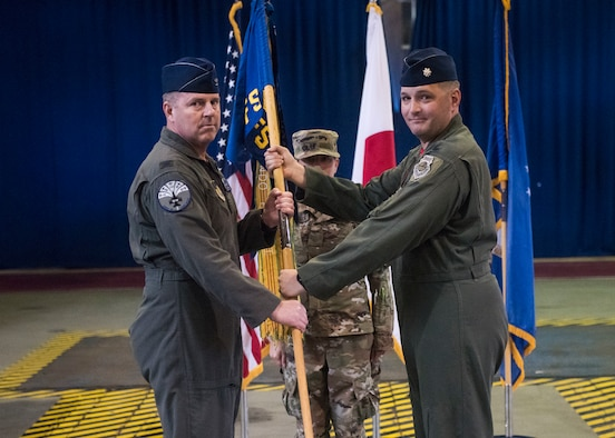 Individuals participate in a change of command ceremony indoors