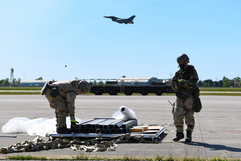U.S. Airmen from the 724th Air Mobility Squadron unload cargo during a Nodal Lightning exercise at Aviano Air Base, Italy, May 18, 2021. The exercise started with a simulated air attack followed by other attacks and injuries to teammates. (U.S. Air Force photo by Airman 1st Class Thomas S. Keisler IV)