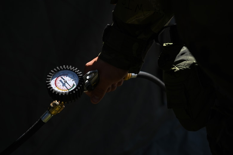 A U.S. Airman with the 724th Air Mobility Squadron (AMS) fills an inflatable tent during Nodal Lightning at Aviano Air Base, Italy, May 18, 2021. Nodal Lightning is a readiness exercise that demonstrates how the 724th AMS would operate in a contested environment. (U.S. Air Force photo by Airman 1st Class Thomas S. Keisler IV)