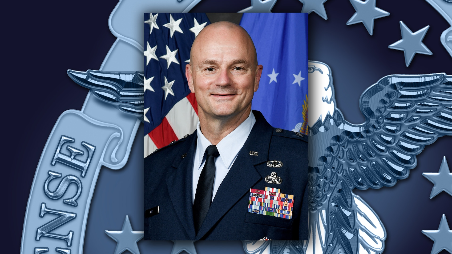 Man in Air Force dress uniform poses in front of a the US and DLA flags.