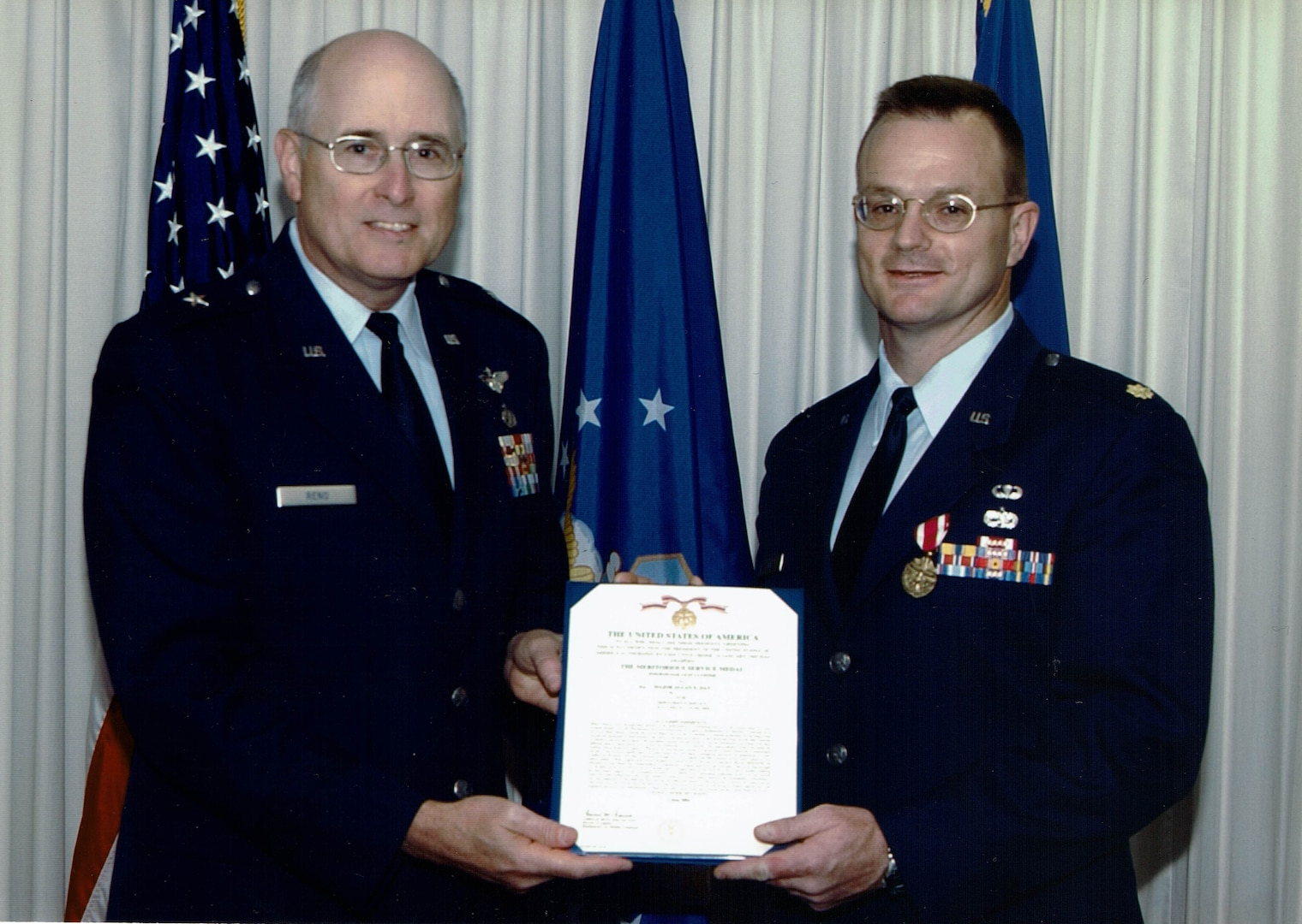 Two man in dress uniforms stand in front of the US and DLA flags holding a certificate.